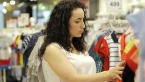 Ένα ελκυστικό brunette επιλέγει ένα kombenizon για μια μικρή κόρη σε ένα κατάστημα Όμορφη γυναίκα σε έναν ιματισμό παιδιών ` s απόθεμα βίντεο