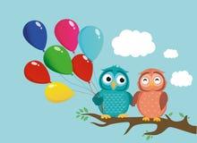 Ένα ζευγάρι της χαριτωμένης συνεδρίασης owlet σε έναν κλάδο και της εκμετάλλευσης πολλά μπαλόνια Στοκ Εικόνα