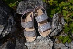 Ένα ζευγάρι του νέου κοιτάγματος εγκατέλειψε τα σανδάλια του κοριτσιού sparkly που αφέθηκαν πίσω τους βράχους στοκ εικόνες