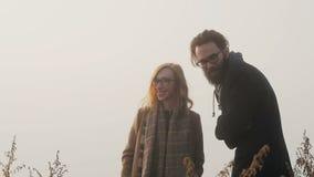 Ένα ζευγάρι του hipster με τα γυαλιά που γελούν στο υπόβαθρο του ηλιοβασιλέματος απόθεμα βίντεο