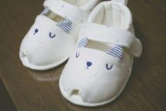 Ένα ζευγάρι των άσπρων παπουτσιών μωρών στον ξύλινο πίνακα στοκ φωτογραφίες με δικαίωμα ελεύθερης χρήσης