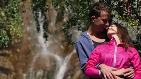 Ένα ζευγάρι των εραστών στέκεται ενάντια σε έναν καταρράκτη honeymoon φιλί στο υπόβαθρο των βουνών οικογενειακά καρύδια έννοιας σ φιλμ μικρού μήκους