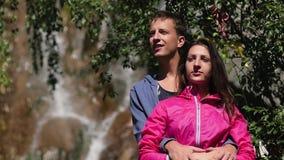 Ένα ζευγάρι των εραστών στέκεται ενάντια σε έναν καταρράκτη honeymoon φιλί στο υπόβαθρο των βουνών οικογενειακά καρύδια έννοιας σ απόθεμα βίντεο