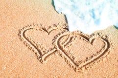 Ένα ζευγάρι των καρδιών που χρωματίζονται στην άμμο το καλοκαίρι στη θάλασσα Στοκ Φωτογραφίες
