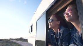 Ένα ζευγάρι των νέων γυναικών που ντύνονται στα τζιν φαίνεται έξω το παράθυρο ενός autotrailer φιλμ μικρού μήκους