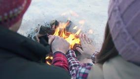 Ένα ζευγάρι των νέων με τα γαμήλια δαχτυλίδια στα χειμερινά ενδύματα στα ξύλα, θερμαίνει τα χέρια τους από την πυρκαγιά, χειμεριν φιλμ μικρού μήκους
