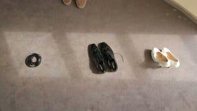 Ένα ζευγάρι των νυφικών παπουτσιών των ανδρών και των γυναικών και της ζώνης του νεόνυμφου στο υπόβαθρο πατωμάτων Γαμήλιες ιδιότη φιλμ μικρού μήκους