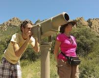 Ένα ζευγάρι των οδοιπόρων χρησιμοποιεί ένα τηλεσκόπιο στοκ φωτογραφία