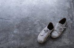 Ένα ζευγάρι των παλαιών βρώμικων παπουτσιών στο πάτωμα τσιμέντου με το φως που σκιάζει από τη γωνία Στοκ Εικόνες
