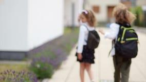 Ένα ζευγάρι των σγουρών μαθητών, ενός αγοριού και ενός κοριτσιού, για παράδειγμα αντίο, που κυματίζουν τα χέρια τους, εξετάζοντας απόθεμα βίντεο