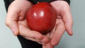 Ένα ζευγάρι των χεριών που κρατά ένα μήλο Στοκ Φωτογραφίες