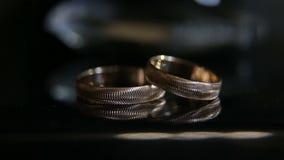 Ένα ζευγάρι των χρυσών δαχτυλιδιών αρραβώνων στο τεχνητό φως απόθεμα βίντεο