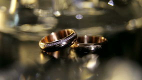 Ένα ζευγάρι των χρυσών δαχτυλιδιών αρραβώνων στο τεχνητό φως closeup απόθεμα βίντεο