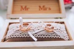 Ένα ζευγάρι των χρυσών γαμήλιων δαχτυλιδιών που βρίσκονται σε ένα άσπρο ξύλινο κιβώτιο γάμος κορδελλών πρόσκλησης λουλουδιών κομψ Στοκ εικόνες με δικαίωμα ελεύθερης χρήσης