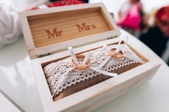Ένα ζευγάρι των χρυσών γαμήλιων δαχτυλιδιών που βρίσκονται σε ένα άσπρο ξύλινο κιβώτιο γάμος κορδελλών πρόσκλησης λουλουδιών κομψ Στοκ Εικόνες
