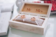 Ένα ζευγάρι των χρυσών γαμήλιων δαχτυλιδιών που βρίσκονται σε ένα άσπρο ξύλινο κιβώτιο γάμος κορδελλών πρόσκλησης λουλουδιών κομψ Στοκ Εικόνα