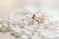 Ένα ζευγάρι των χρυσών γαμήλιων δαχτυλιδιών στα μαργαριτάρια Στοκ εικόνες με δικαίωμα ελεύθερης χρήσης