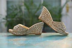 Ένα ζευγάρι των χρυσών σανδαλιών νυφών glittery συμπαθητικών υψηλών βάζει τακούνια στο μοντέρνο σχέδιο toe τιτιβίσματος στοκ εικόνες