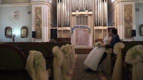 Ένα ζευγάρι των newlyweds που φιλούν τη συνεδρίαση στο ναό φιλμ μικρού μήκους