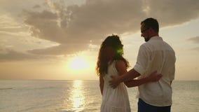 Ένα ζεύγος ερωτευμένο θαυμάζει το ηλιοβασίλεμα πέρα από τη θάλασσα υποστηρίξτε την όψη βίντεο 10 μπιτ φιλμ μικρού μήκους