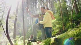 Ένα ζεύγος ερωτευμένο των ταξιδιωτών με τα σακίδια πλάτης φωτογραφίζεται στο δάσος τις ακτίνες του ήλιου πρωινού υπέροχα απόθεμα βίντεο