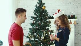 Ένα ζεύγος διακοσμεί ένα χριστουγεννιάτικο δέντρο απόθεμα βίντεο
