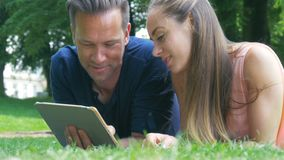 Ένα ζεύγος που καταψύχει στο πάρκο, φωτογραφίες προσοχής στην ταμπλέτα τους και ταχυδρόμηση στα κοινωνικά δίκτυα απόθεμα βίντεο