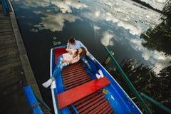 Ένα ζεύγος που οδηγά μια μπλε βάρκα σε μια λίμνη ρωμανικός ζεύγος συναισθηματικό αστείος και ερωτευμένος στοκ εικόνα