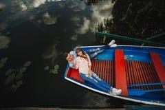 Ένα ζεύγος που οδηγά μια μπλε βάρκα σε μια λίμνη ρωμανικός ζεύγος συναισθηματικό αστείος και ερωτευμένος στοκ εικόνες