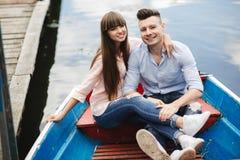 Ένα ζεύγος που οδηγά μια μπλε βάρκα σε μια λίμνη ρωμανικός ζεύγος συναισθηματικό αστείος και ερωτευμένος στοκ φωτογραφίες