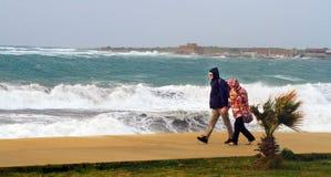 Ένα ζεύγος που περπατά κοντά στη θάλασσα στη θύελλα στοκ εικόνα