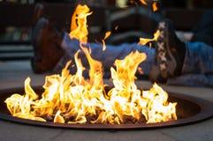 Ένα ζεύγος που χαλαρώνει από την υπαίθρια πυρκαγιά σε ένα χωριό σκι Στοκ Φωτογραφία