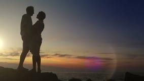 Ένα ζεύγος στέκεται στο βάραθρο στο ηλιοβασίλεμα και το φιλί απόθεμα βίντεο