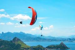 Ένα ζωηρόχρωμο αλεξίπτωτο με το skydiver σε ένα ηλιόλουστο υπόβαθρο μπλε ουρανού ενεργός τρόπος ζωής ακραίος αθλητισμός Η έννοια  στοκ φωτογραφία