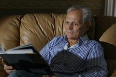 Ένα ηλικιωμένο άτομο που χαμογελά εξετάζει μια φωτογραφία σε ένα λεύκωμα στοκ φωτογραφία
