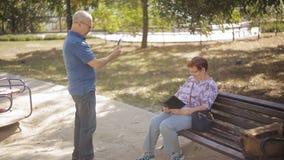 Ένα ηλικιωμένο άτομο φωτογραφίζεται στο τηλέφωνο την ηλικίας σύζυγό του στο πάρκο φιλμ μικρού μήκους