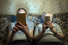 Ένα ηλικιωμένο ζεύγος κάθεται στον καναπέ με τις συσκευές, εξετάζει το στοκ εικόνες