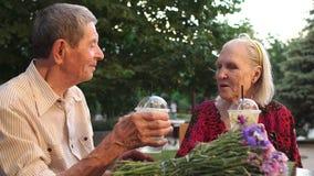 Ένα ηλικιωμένο ζεύγος κάθεται στον καφέ με τη λεμονάδα απόθεμα βίντεο