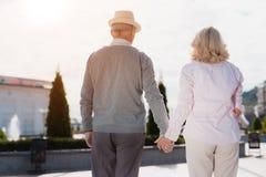 Ένα ηλικιωμένο ζεύγος περπατά γύρω από τα χέρια εκμετάλλευσης Περπατούν κατά μήκος ενός όμορφου τετραγώνου Στοκ εικόνα με δικαίωμα ελεύθερης χρήσης