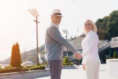 Ένα ηλικιωμένο ζεύγος περπατά γύρω από τα χέρια εκμετάλλευσης Περπατούν κατά μήκος ενός όμορφου τετραγώνου Στοκ Εικόνες
