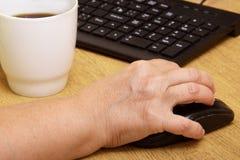 Ένα ηλικιωμένο χέρι γυναικών σε ένα ποντίκι υπολογιστών Η παλαιά γιαγιά εργάζεται πίσω από το πληκτρολόγιο υπολογιστών και πίνει  Στοκ Εικόνες