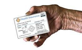 Ένα ηλικιωμένο χέρι κρατά μια κάρτα ταυτότητας ιατρικής ασφάλειας για να επεξηγήσει την υγειονομική περίθαλψη στοκ εικόνα με δικαίωμα ελεύθερης χρήσης