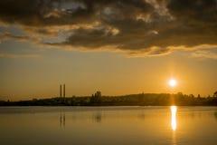 Ένα ηλιοβασίλεμα πέρα από το νερό Εργοστάσιο με δύο καπνοδόχους στοκ φωτογραφία με δικαίωμα ελεύθερης χρήσης