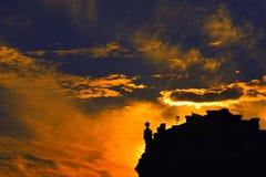 Ένα ηλιοβασίλεμα σε μια πόλη με μια σκιαγραφία ενός κτηρίου και πορτοκαλιών ουρανών πέρα από το Στοκ φωτογραφία με δικαίωμα ελεύθερης χρήσης