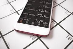 Ένα ημερολόγιο και ένας παγκόσμιος χρόνος app σε ένα κινητό τηλέφωνο χρησιμοποιούνται για τον προγραμματισμό ταξιδιού στις διαφορ Στοκ εικόνα με δικαίωμα ελεύθερης χρήσης