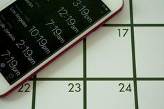 Ένα ημερολόγιο και ένας παγκόσμιος χρόνος app σε ένα κινητό τηλέφωνο χρησιμοποιούνται για τον προγραμματισμό ταξιδιού στις διαφορ Στοκ φωτογραφία με δικαίωμα ελεύθερης χρήσης