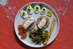 Ένα δημιουργικό πιάτο των ορεκτικών σε ένα κόκκινο επιτραπέζιο ύφασμα Στοκ Εικόνα