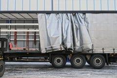 Ένα ημιρυμουλκούμενο όχημα με έναν εκτεθειμένο μουσαμά κατά τη διάρκεια της εκφόρτωσης Μεταφορά και εκφόρτωση στοκ φωτογραφία