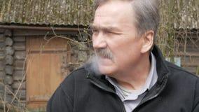 Ένα ηλικιωμένο άτομο με ένα mustache καπνίζει στην οδό κοντά στο παλαιό σπίτι Ντυμένος σε ένα μαύρο πουλόβερ φιλμ μικρού μήκους