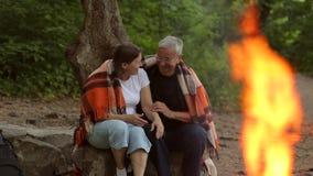 Ένα ηλικιωμένο ζεύγος κάθεται κάτω από ένα κάλυμμα κοντά στην πυρκαγιά φιλμ μικρού μήκους